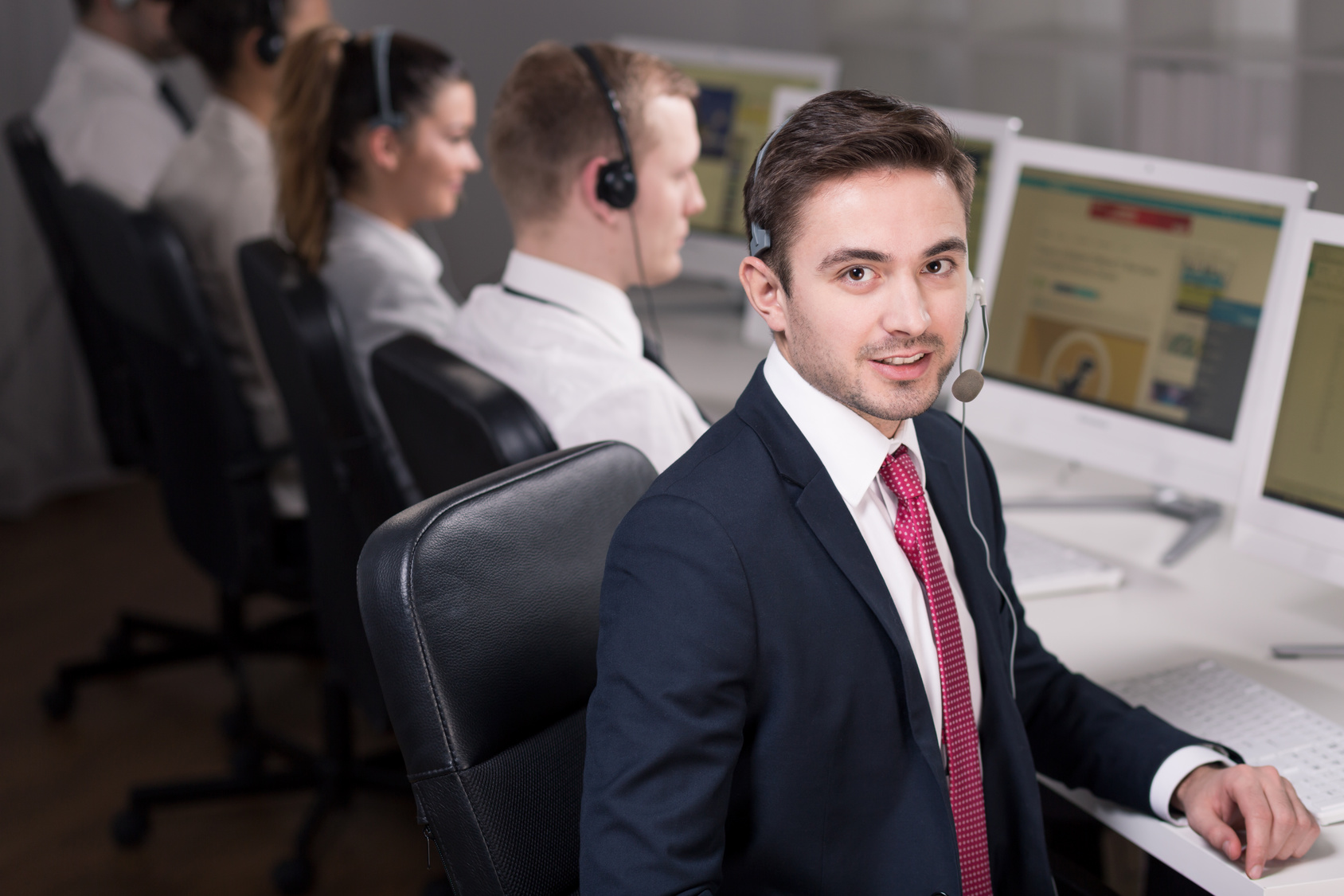 Young smiling salesman working in call center